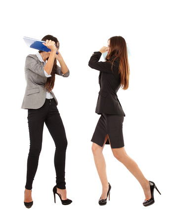 beating: Portrait of businesswomen beating each other with notebooks isolated on white