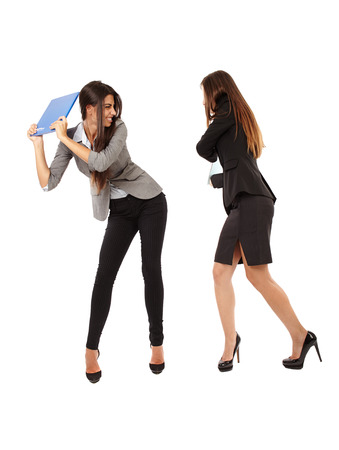 Portrait of businesswomen beating each other with notebooks isolated on white