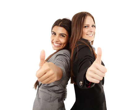 Portrait of businesswomen making thumbs up sign and smiling over white background photo