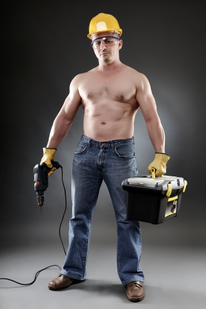 Studio shot of topless handsome worker holding a drill and a toolbox  photo