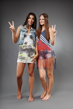 Happy hippies making the victory sign on gray background photo