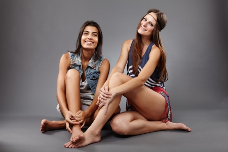 indian style sitting: Happy girlfriends sitting on the floor and having fun together
