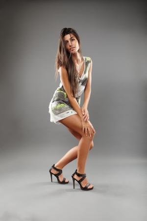 Portrait of sexy indian woman wearing mini dress on gray background photo