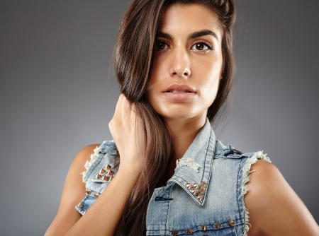 Closeup of young attractive indian woman on gray background photo