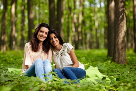 indian summer: Mother and daughter sitting on a blanket at a picnic in the forest
