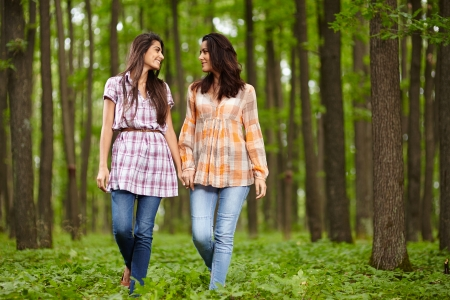 Mother and daughter walking hand in hand through a forest and talking photo
