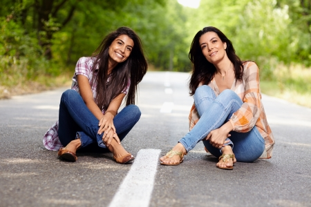Mother and daughter sitting cross legged on the road in a forest photo