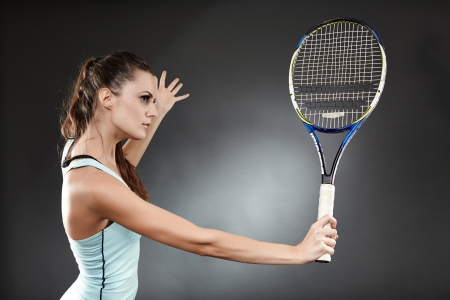 Studio shot of a female tennis player preparing to execute a backhand volley photo