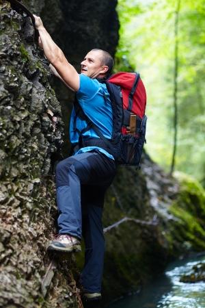 canyon walls: Man climbing mountain wall over a river in a canyon