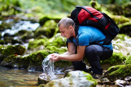 Tourist washing hands in a mountain river photo