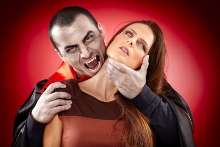 Vampire preparing to bite a beautiful woman's neck photo