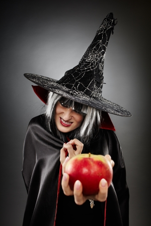 poisoned: Closeup of a spooky witch offering a poisoned apple