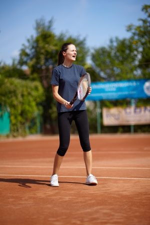 Tennis instructor teaching on a clay court photo