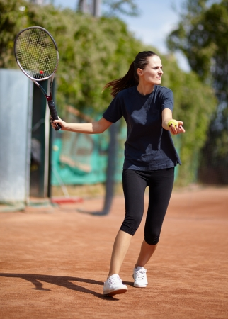Female tennis player executing a forehand  photo