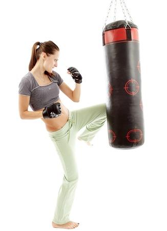 Athletic femme coups de pied le sac de boxe isolé sur blanc Banque d'images
