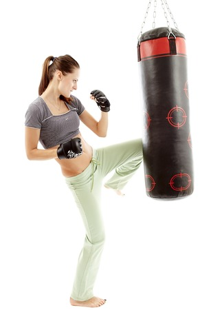 boxers: Athletic woman kicking the punching bag isolated on white Stock Photo