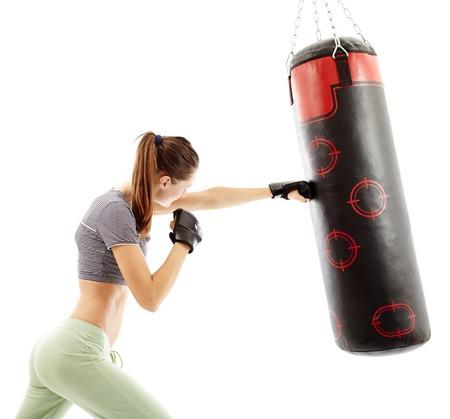 Attractive jeune femme frapper le sac de boxe isolé sur blanc