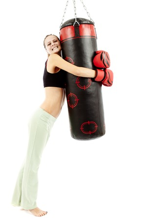 Young athletic beautiful woman hugging a punching bag isolated on white photo