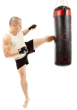 Boxer kicking the punching bag isolated on white photo