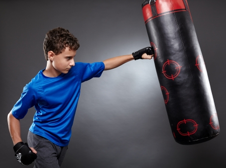 Boy hitting the punching bag on gray background photo