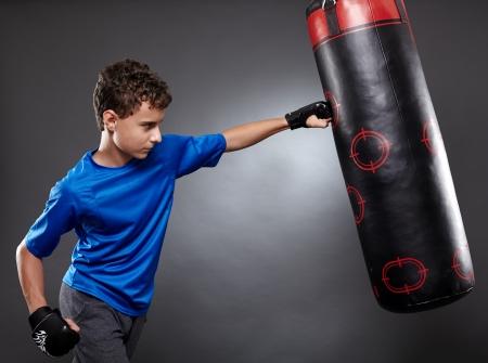 body bag: Boy hitting the punching bag on gray background Stock Photo