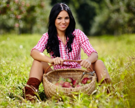 Sexy brunette sitting near a basket of apples in the orchard photo