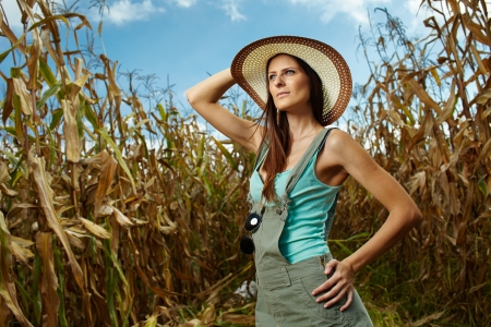 Sexy woman farmer standing in the cornfield at harvest photo