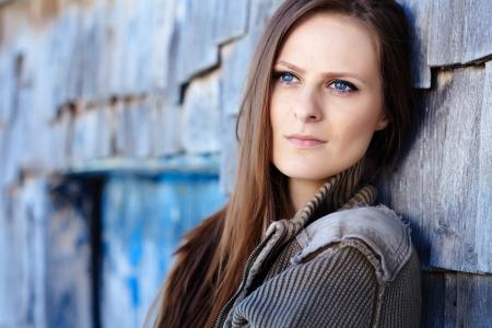 mujer pensativa: Mujer hermosa joven que se inclina en una caba�a de madera con una actitud pensativa