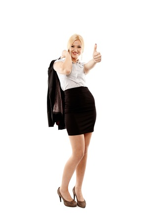 Full length studio portrait of young successfull businesswoman making the finger up sign and holding her coat, isolated on white background photo