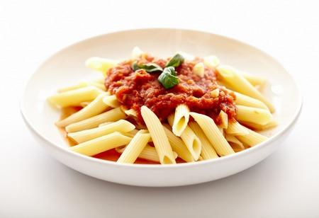 Closeup of italian traditional pasta with tomato sauce, peperoni and basil, penne arrabbiata, isolated on white bakground