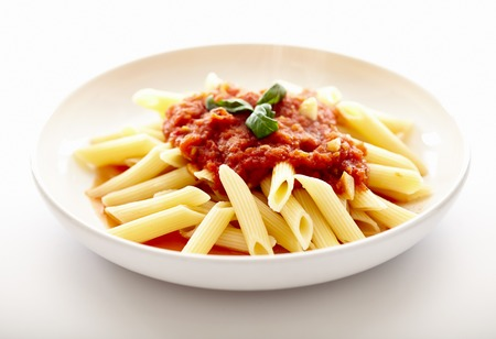 Closeup of italian traditional pasta with tomato sauce, peperoni and basil, penne arrabbiata, isolated on white bakground