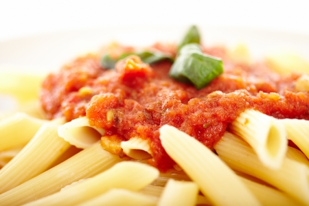 Closeup of traditional italian pasta with tomato and pepperoni sauce decorated with basil, selective focus photo