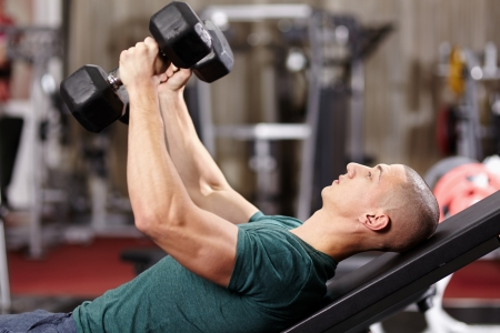 Athletic young man laid on back working his chest with heavy dumbbells Stock Photo