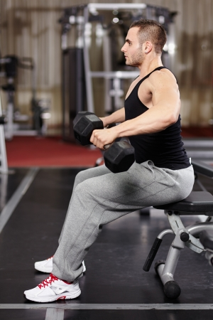 deltoids: Athletic young man working his deltoids with heavy dumbbells at the gym