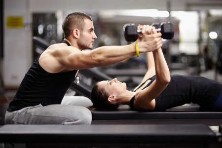 Personal trainer helping woman working with heavy dumbbells Foto de archivo