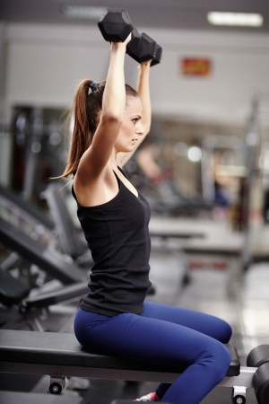 deltoids: Sexy young woman working her arms with dumbbells at the gym