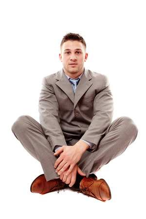 cross ties: Studio portrait of young positive businessman sitting cross legged, isolated on white background