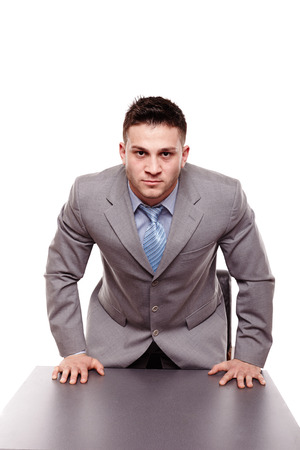 Studio shot of menacing businessman with hands on the desk, isolated over white background Stock Photo