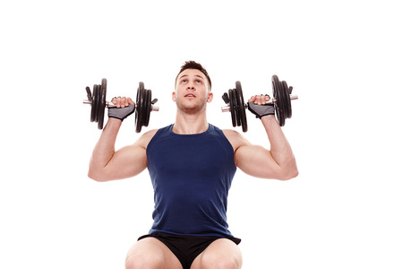 deltoids: Studio portrait of handsome young man working deltoids with heavy dumbbells, isolated over white background