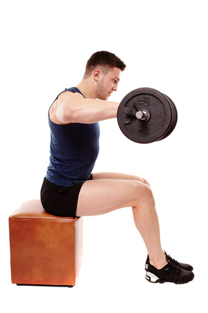 deltoids: Studio shot of handsome young man working deltoids with heavy dumbbells, isolated over white background