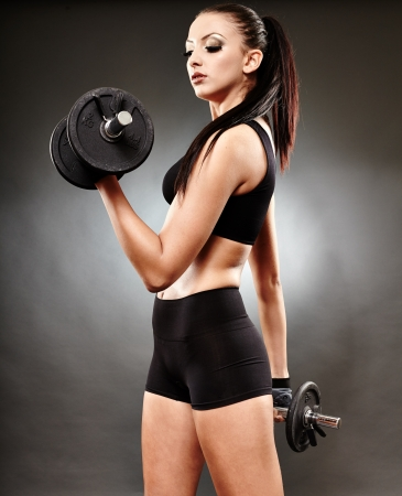 Young athletic woman working her biceps  with heavy dumbbells photo
