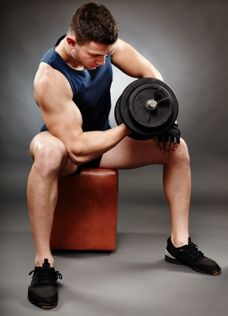 Studio shot of handsome man working with heavy dumbbells photo