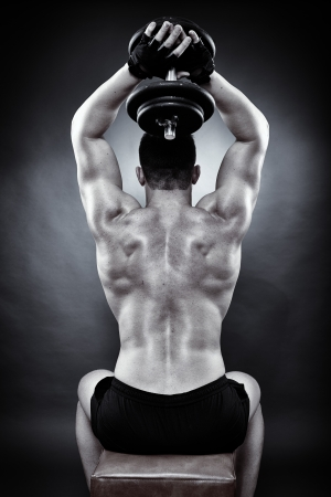 Monochrome shot of athletic young man working with heavy dumbbells
