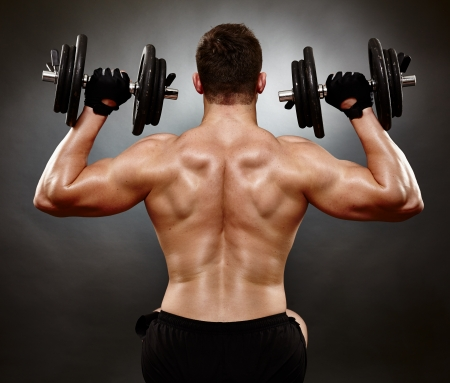 deltoids: Studio shot of athletic young man working his deltoids with heavy dumbbells Stock Photo
