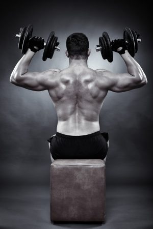Monochrome shot of athletic young man working his deltoids with heavy dumbbells photo