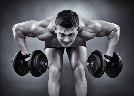 Monochrome shot of young athletic man working with heavy dumbbells photo