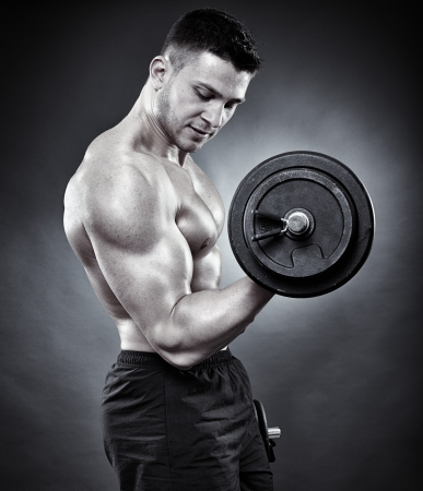 Monochrome shot of young athletic man working out his biceps with heavy dumbbells