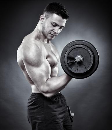 levantando pesas: Monocromo foto de hombre atl�tico joven que trabaja los b�ceps con pesas pesadas Foto de archivo