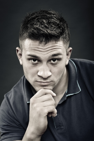Monochrome portrait of handsome young man wearing a navy blue polo t-shirt with hand on chin photo
