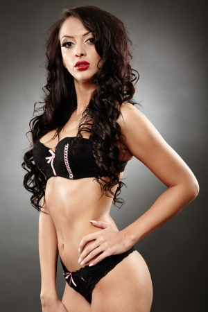 Studio shot of alluring brunette in black lingerie with hand on hip photo